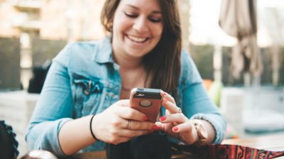 Young-person-smiling-with-phone-and-camera-9nKbMJ