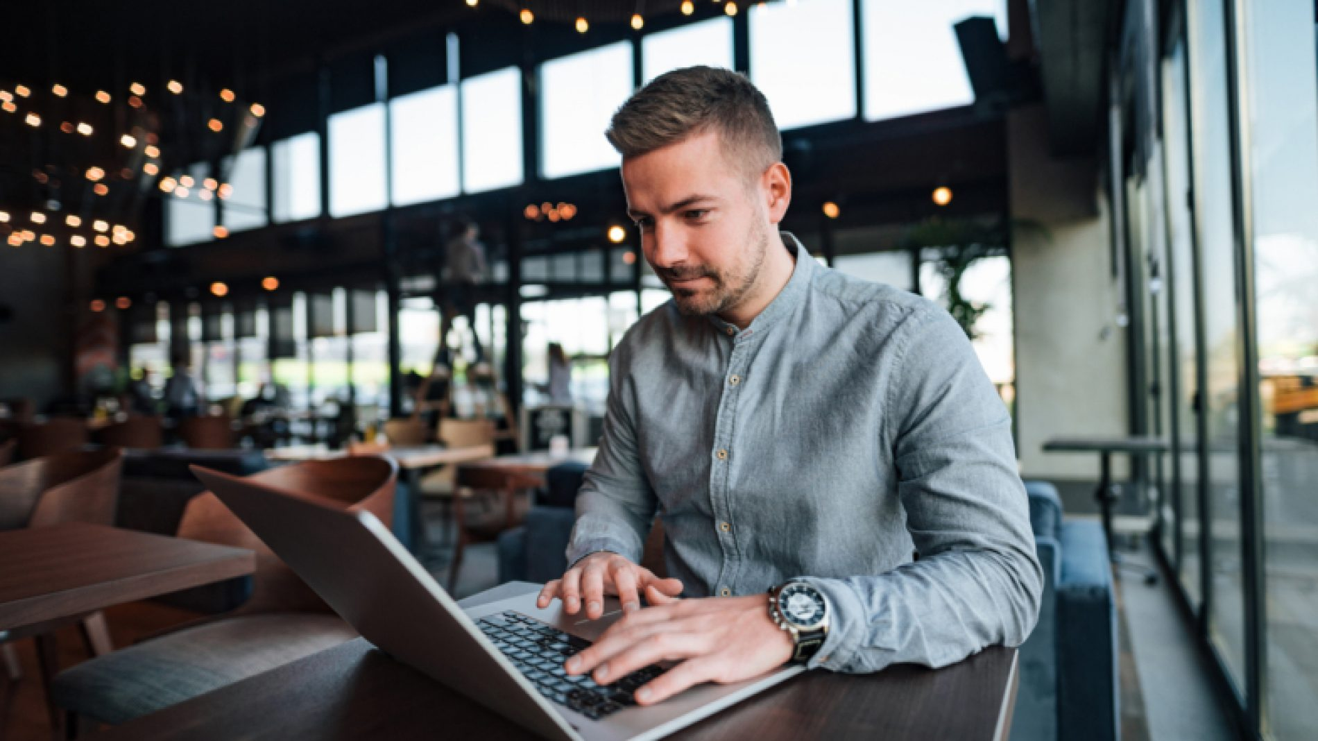 Young-person-tying-on-laptop-in-a-cafe-TE54XA