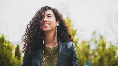 Young person with curly hair and headphones in