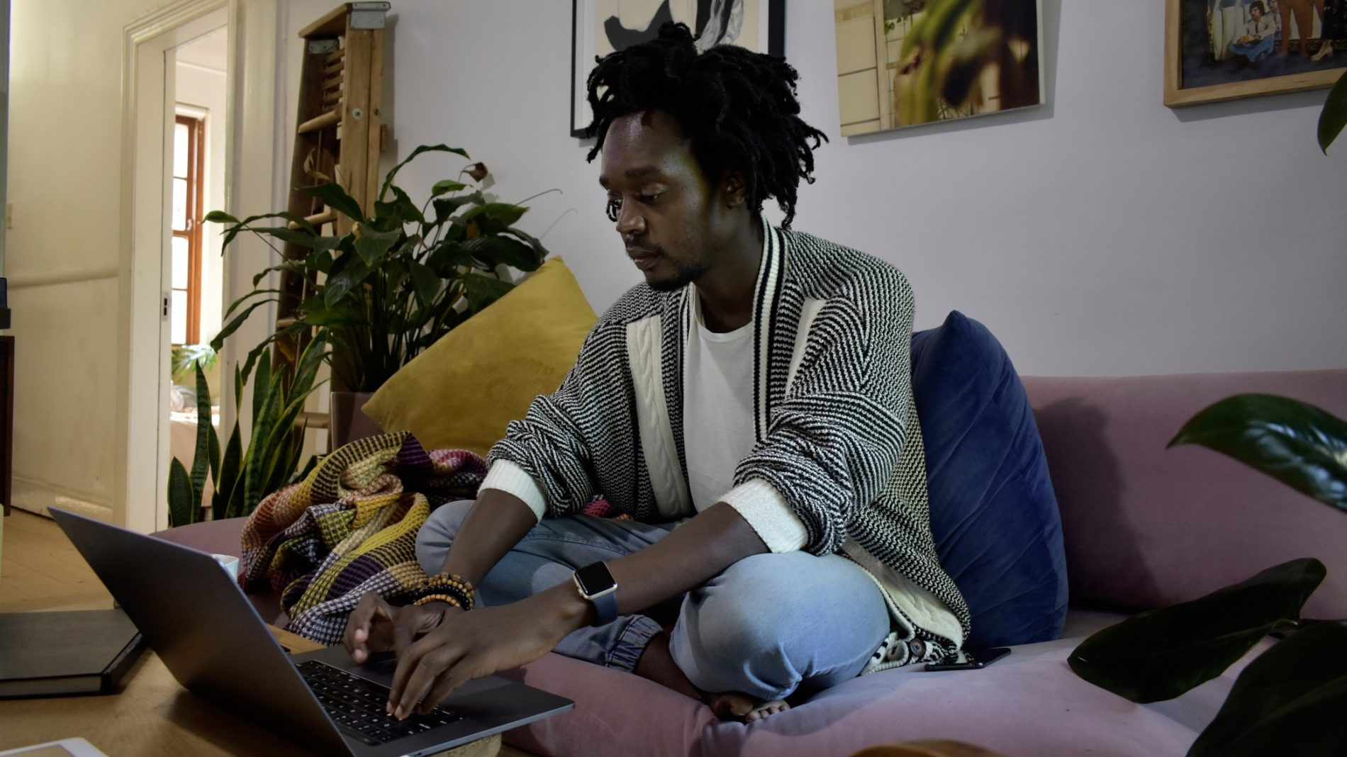 Young person working from their couch at home