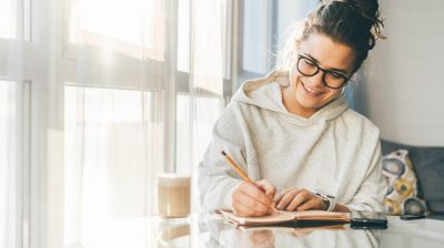 Young person writing and being creative at home