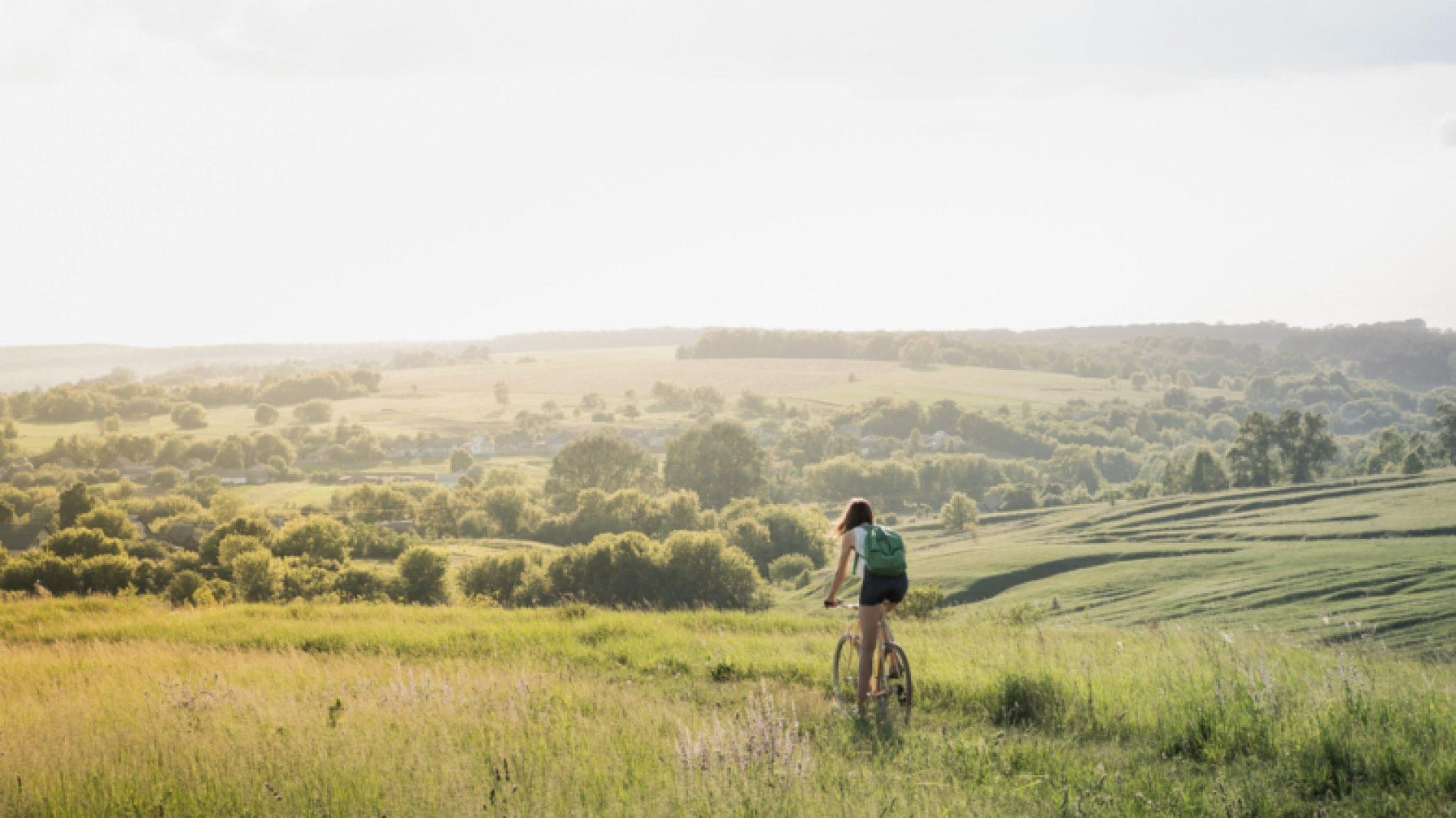 Young-woman-cycling-in-field-KJcaGl
