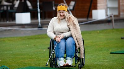 Young woman in a wheelchair playing golf