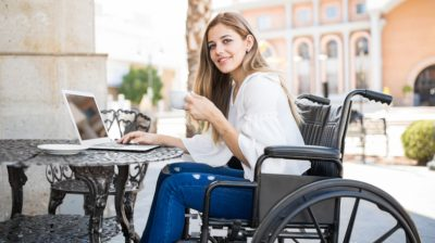Young-woman-in-wheelchair-drinking-tea-with-laptop-aeKfhP