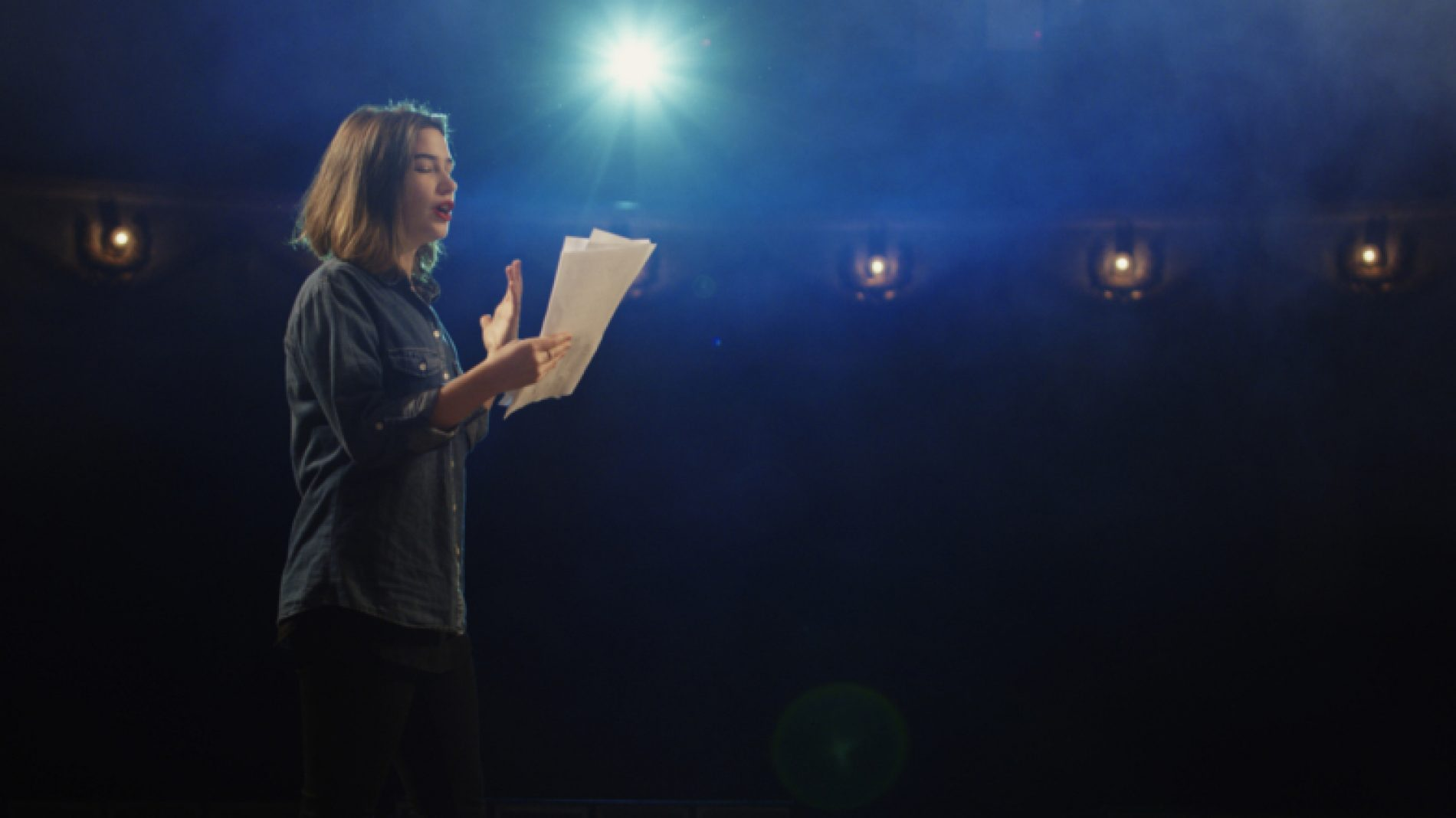 Young-woman-on-stage-with-script-DQzSeV