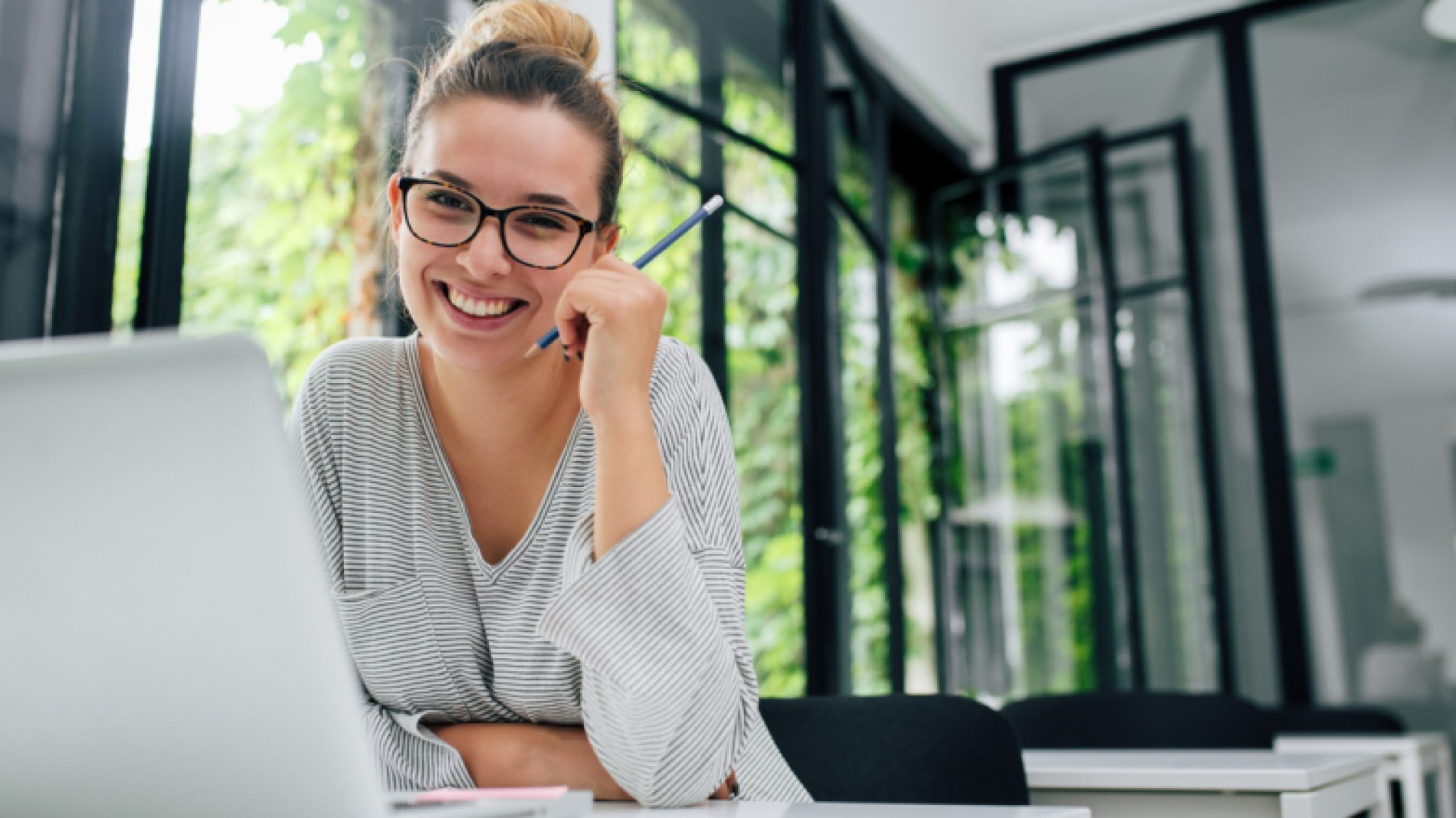 Young-woman-smiling-in-the-library-OGEH4K