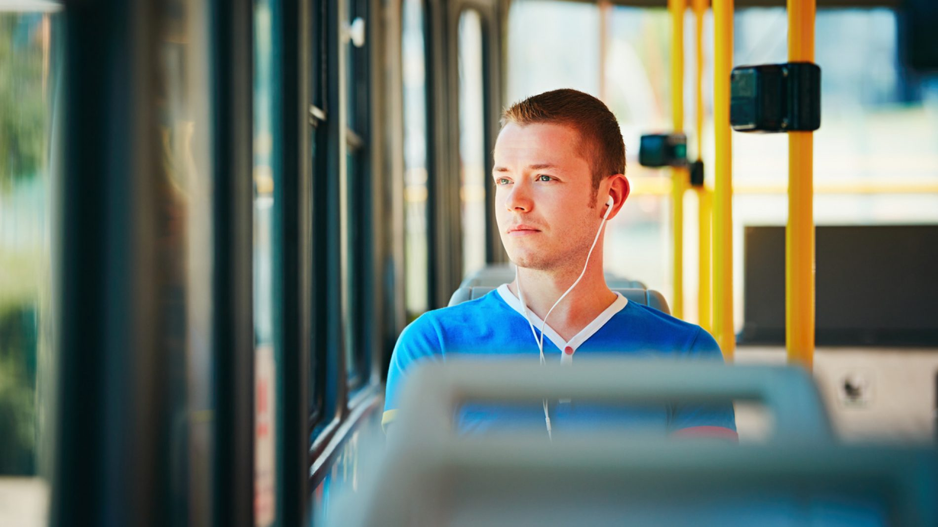Young man listening to music on a bus