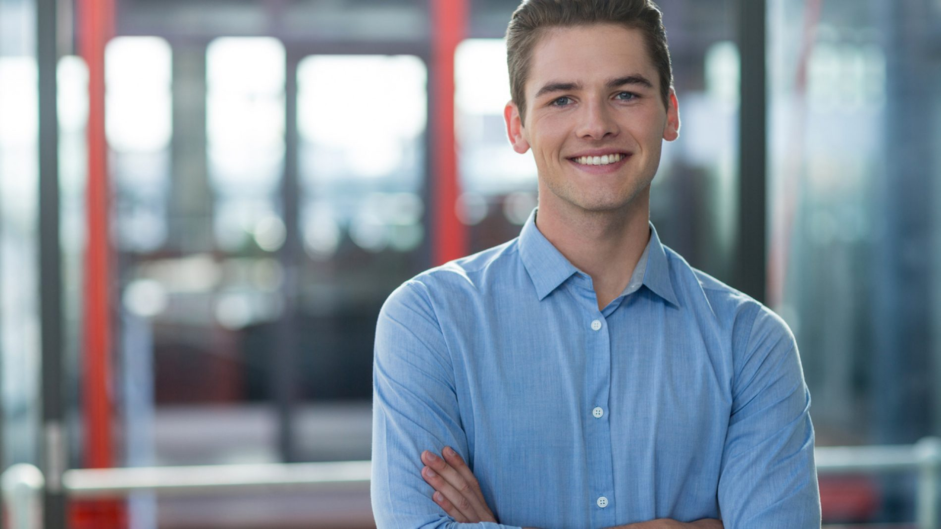 Business executive standing with arms crossed in office