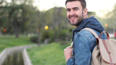 Smiley male holding backpack outdoors with copyspace