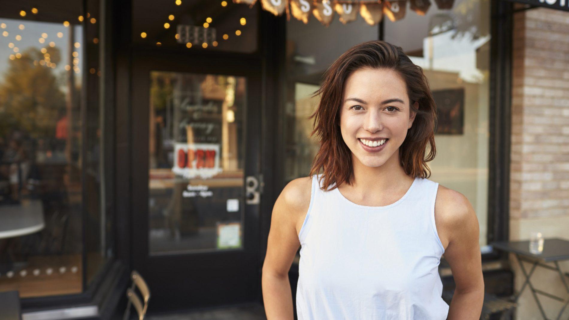 Women standing outside coffee shop smiling