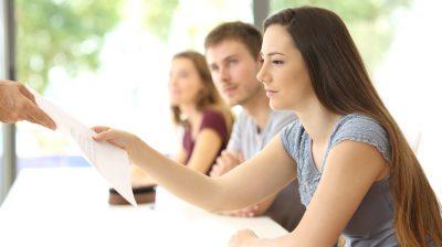 Student receiving an exam from the teacher