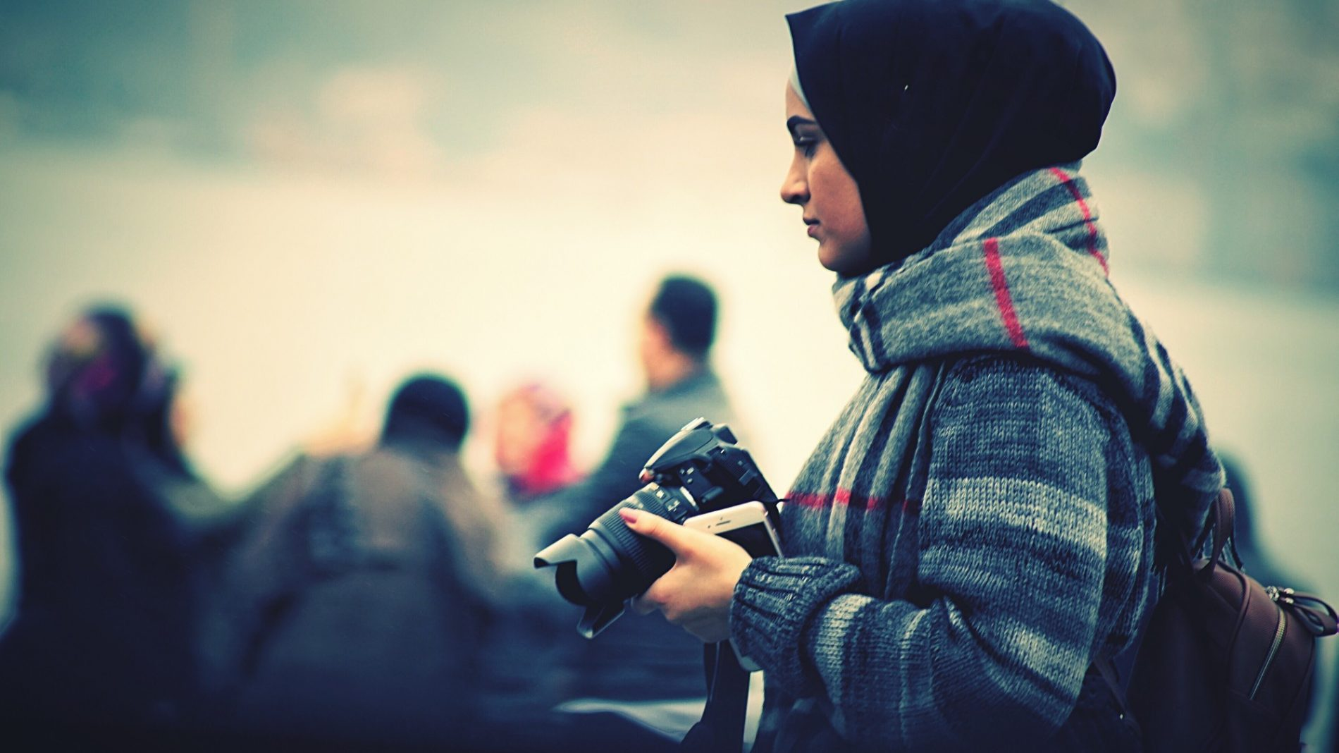 A young woman holding a camera