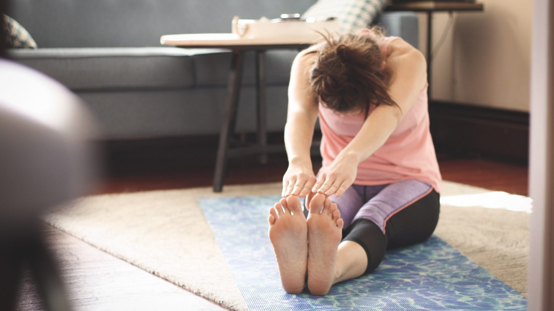 a-woman-stretching-on-a-yoga-mat-in-workout-gear-in-her-home_t20_Bla7vv
