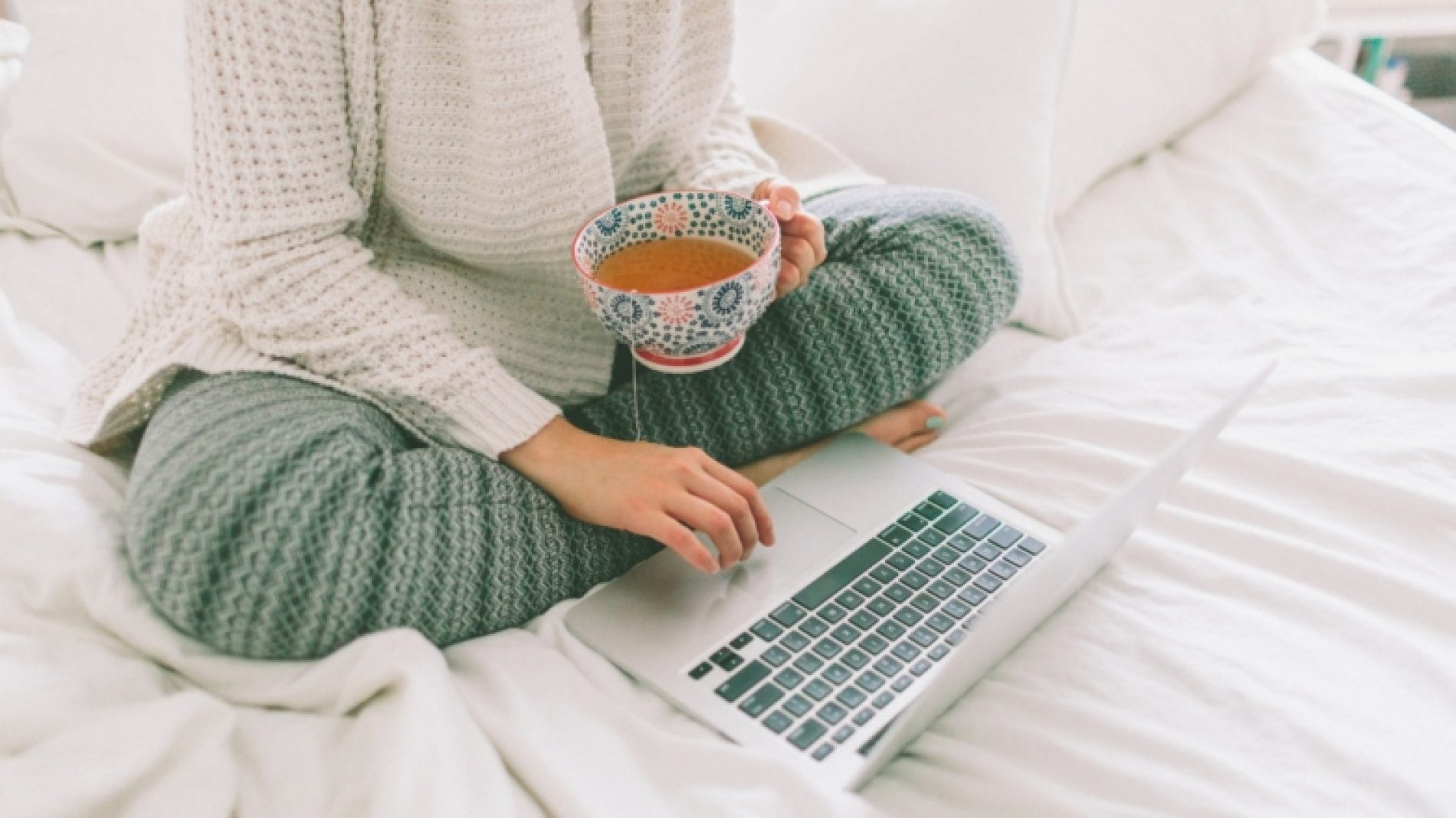 a-woman-working-on-her-laptop-from-her-bed-while-drinking-tea_t20_W7nvng-Bthhh6