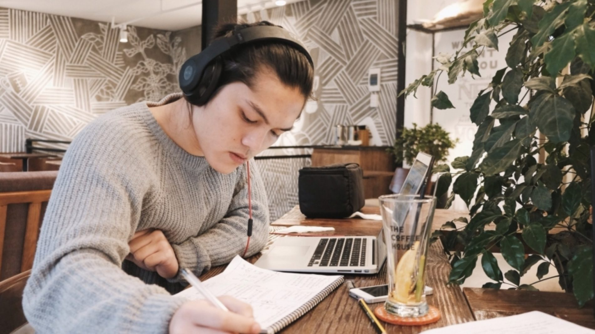a-young-man-studying-and-listening-to-music-at-the-cafeteria_t20_d1Wbzo-vG41vI