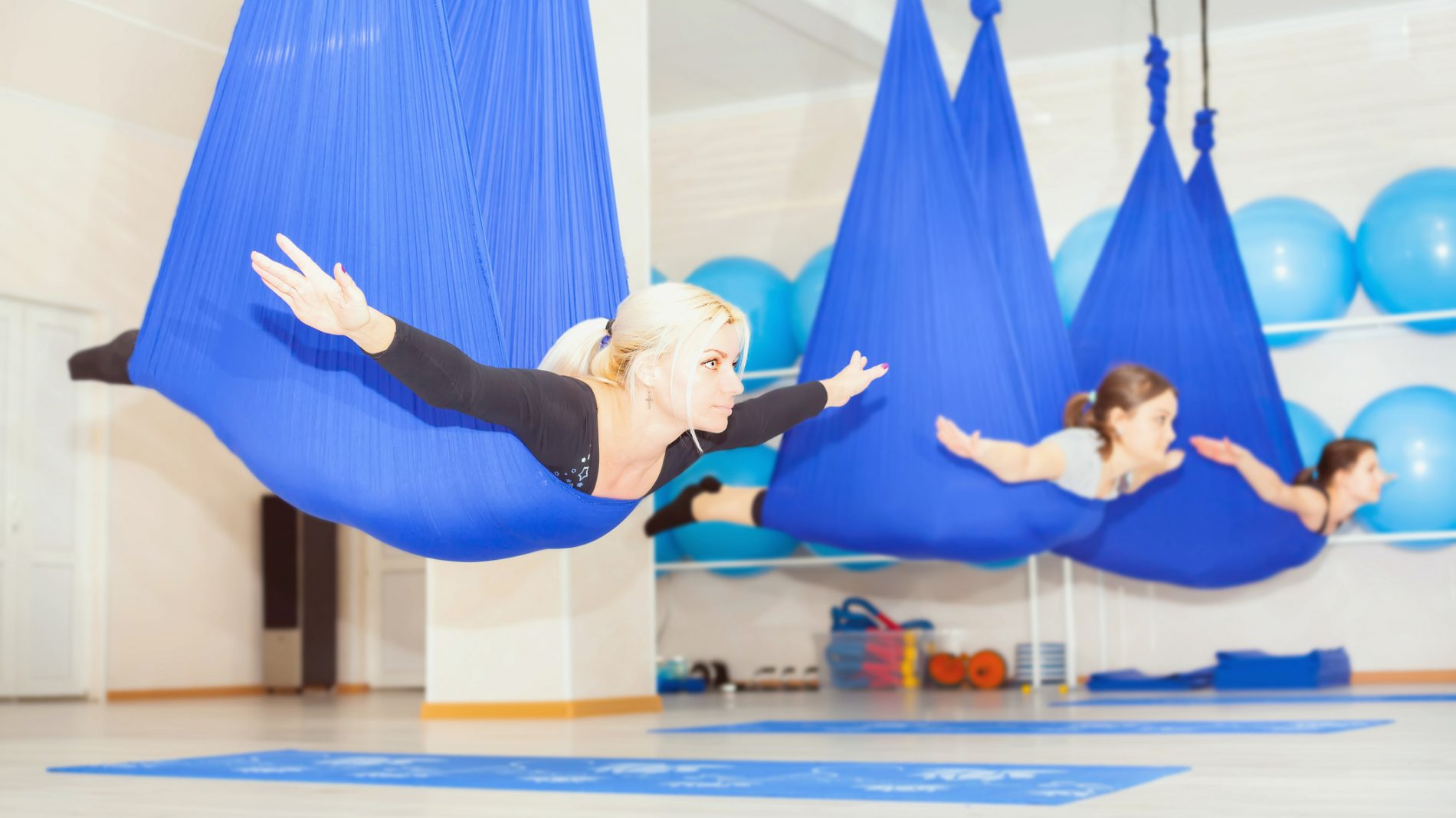 Young women doing aerial yoga exercise or antigravity yoga