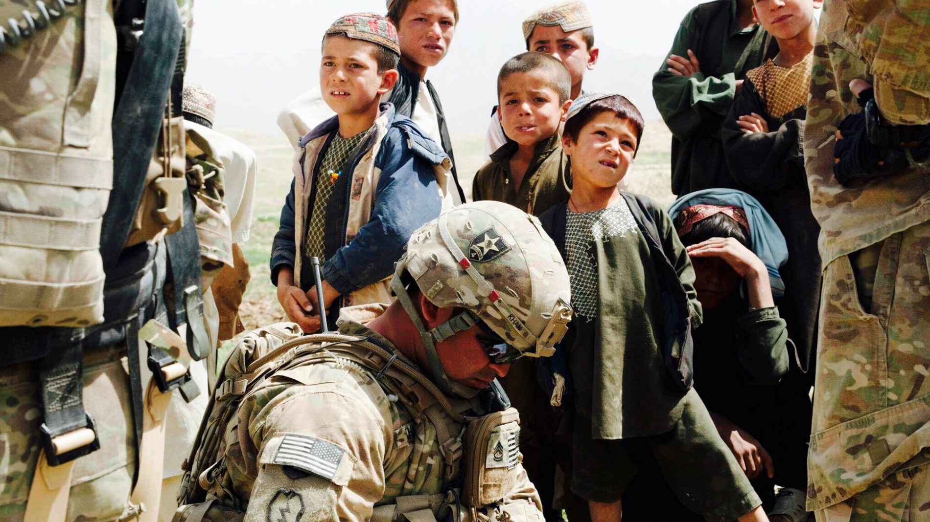 Soldier surrounded by afghan children longest war