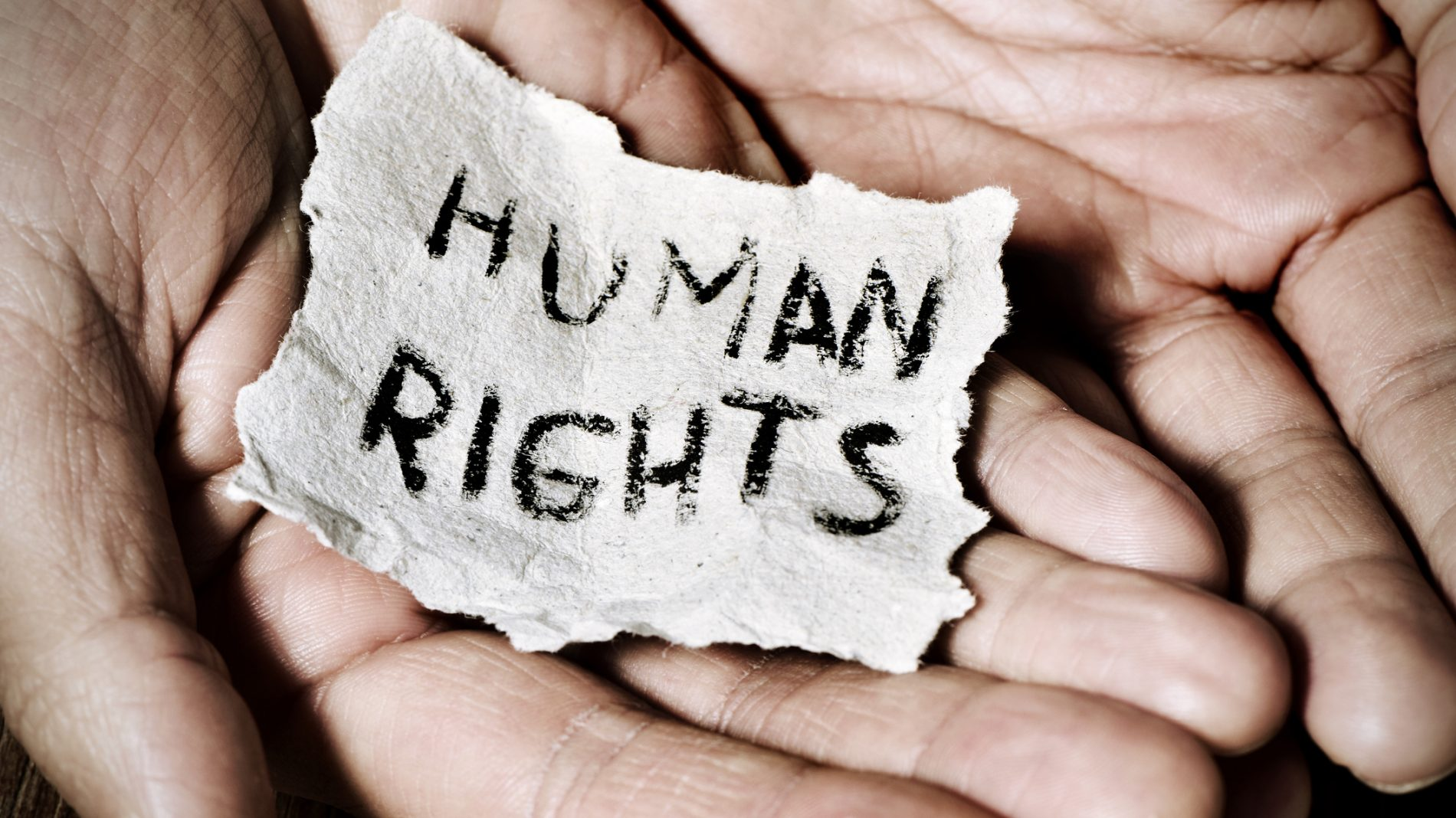 hands holding piece of paper saying HUMAN RIGHTS