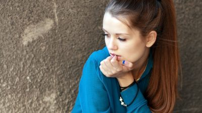 A girl in a blue shirt sitting against a concrete wall