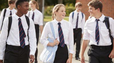 Group Of Teenage Students In Uniform Outside School Buildings