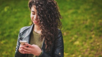 beautiful-young-girl-with-curly-hair-using-mobile-phone-in-the-park_t20_JYGaA4
