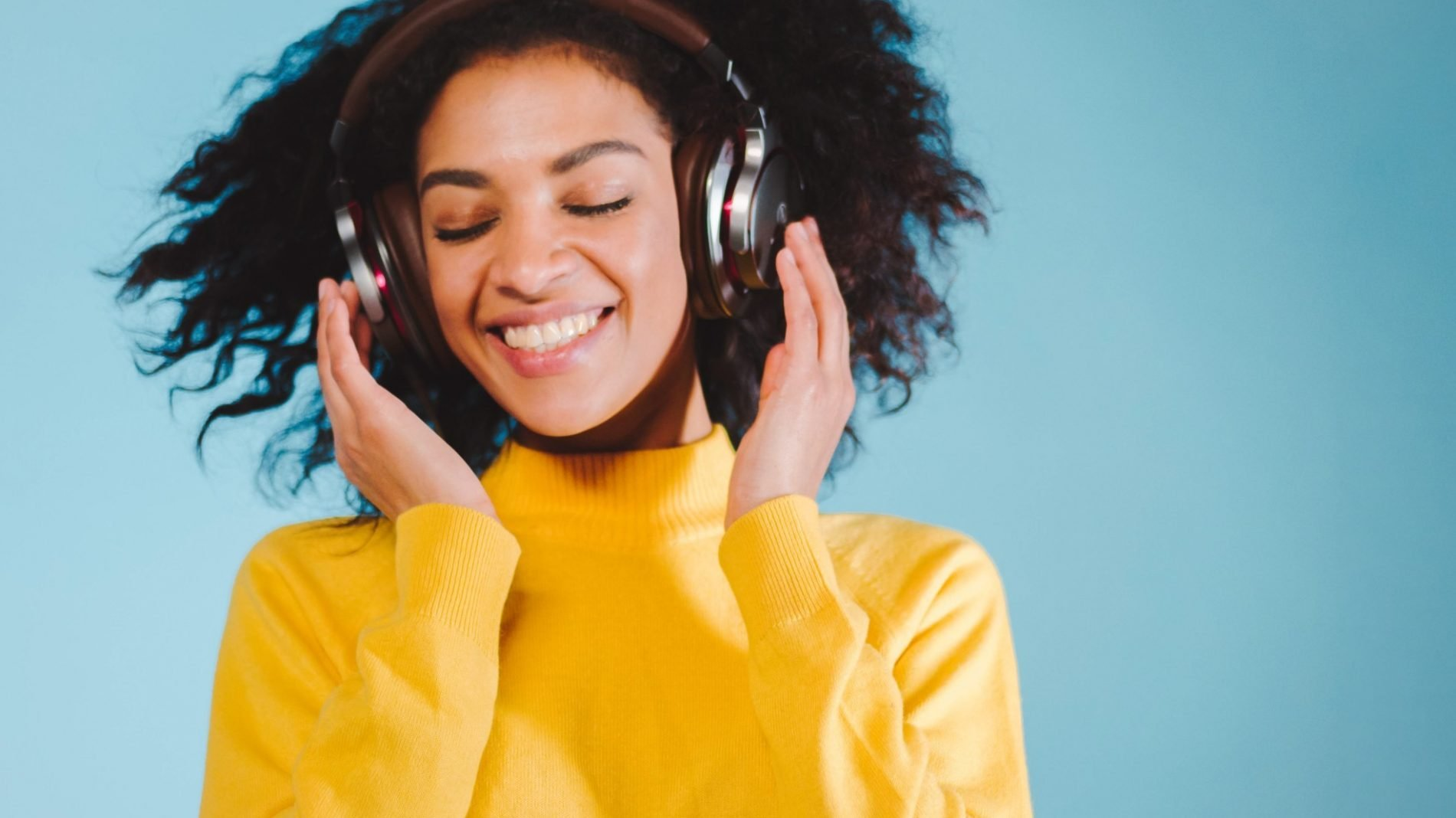 A young woman wearing headphones and listening to music