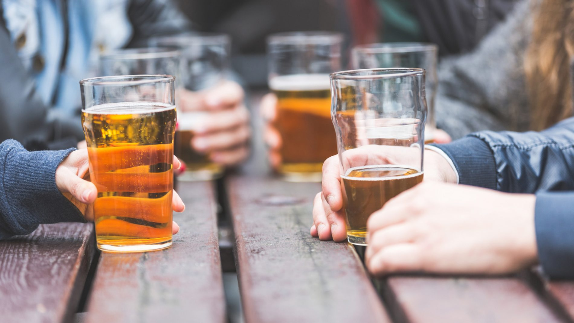 Hands holding glasses with beer on a table in London