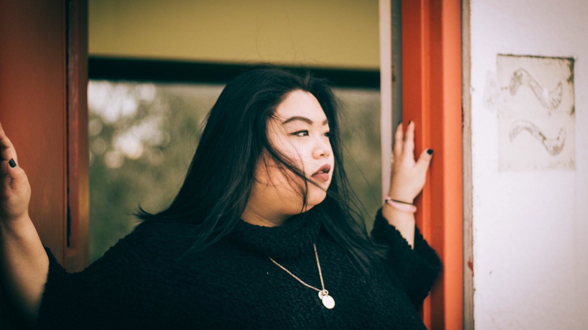 young woman with dark hair standing in doorway