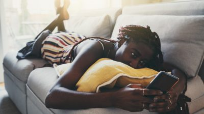 Photograph of a person lying on the couch and looking at their phone