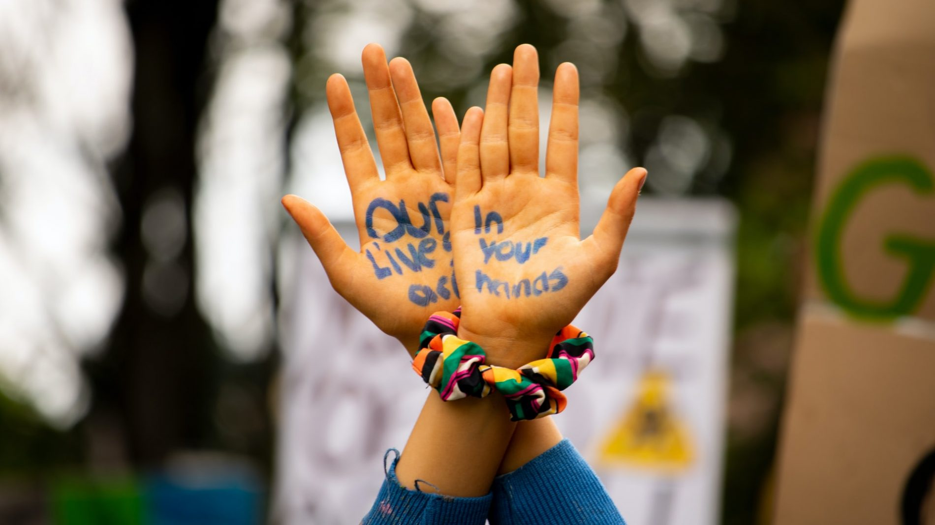 A young person holds their hands in the air. They have
