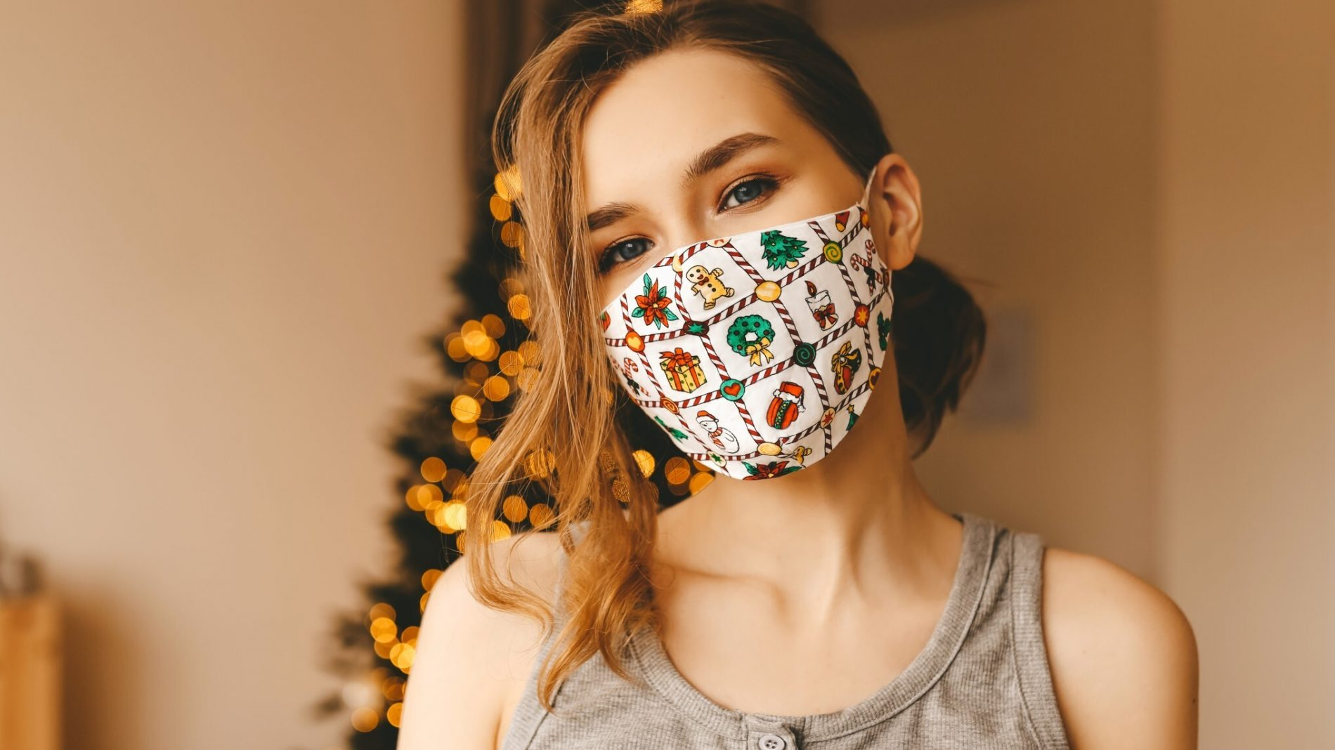 A young woman wearing a face mask in front of a Christmas tree
