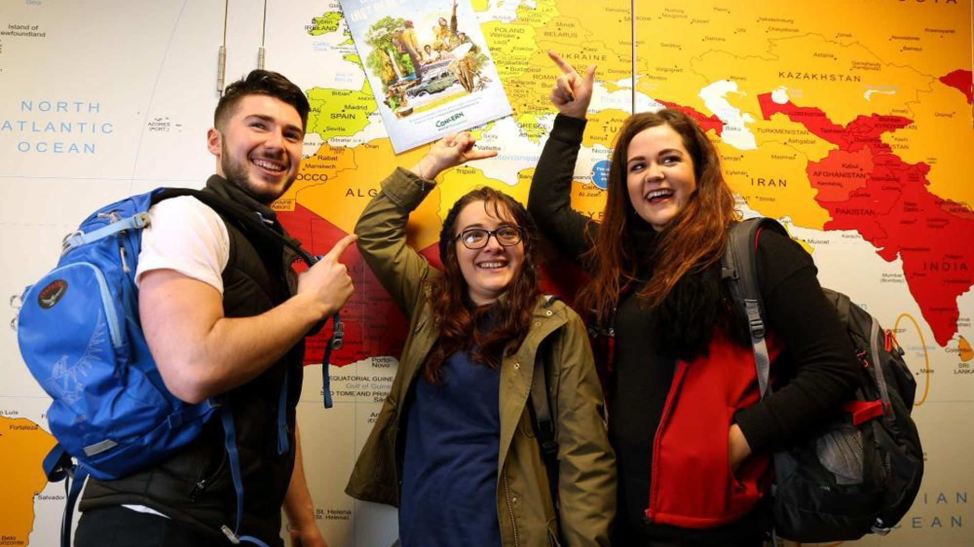 group of young people in front of a map