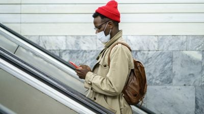 Photo of a person standing on an escalator wearing a face mask and looking at their phone