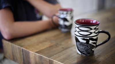 Photo of a person sitting at a table with two mugs in front of them