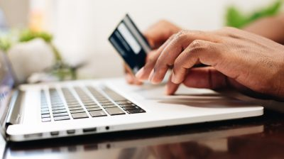 Photo of a person's hands on a laptop with a credit card in one hand