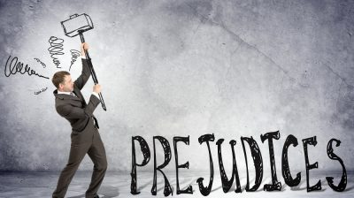 Businessman with hammer and word prejudices on grey wall background