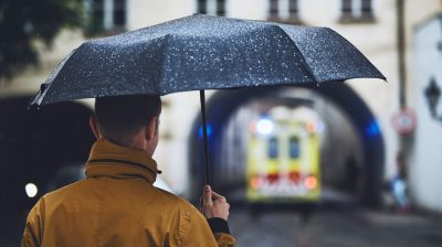 A man standing in the rain with an umbrella looking for emergency accommodation