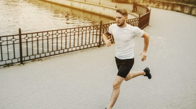 Healthy young caucasian man running in the morning in the park.
