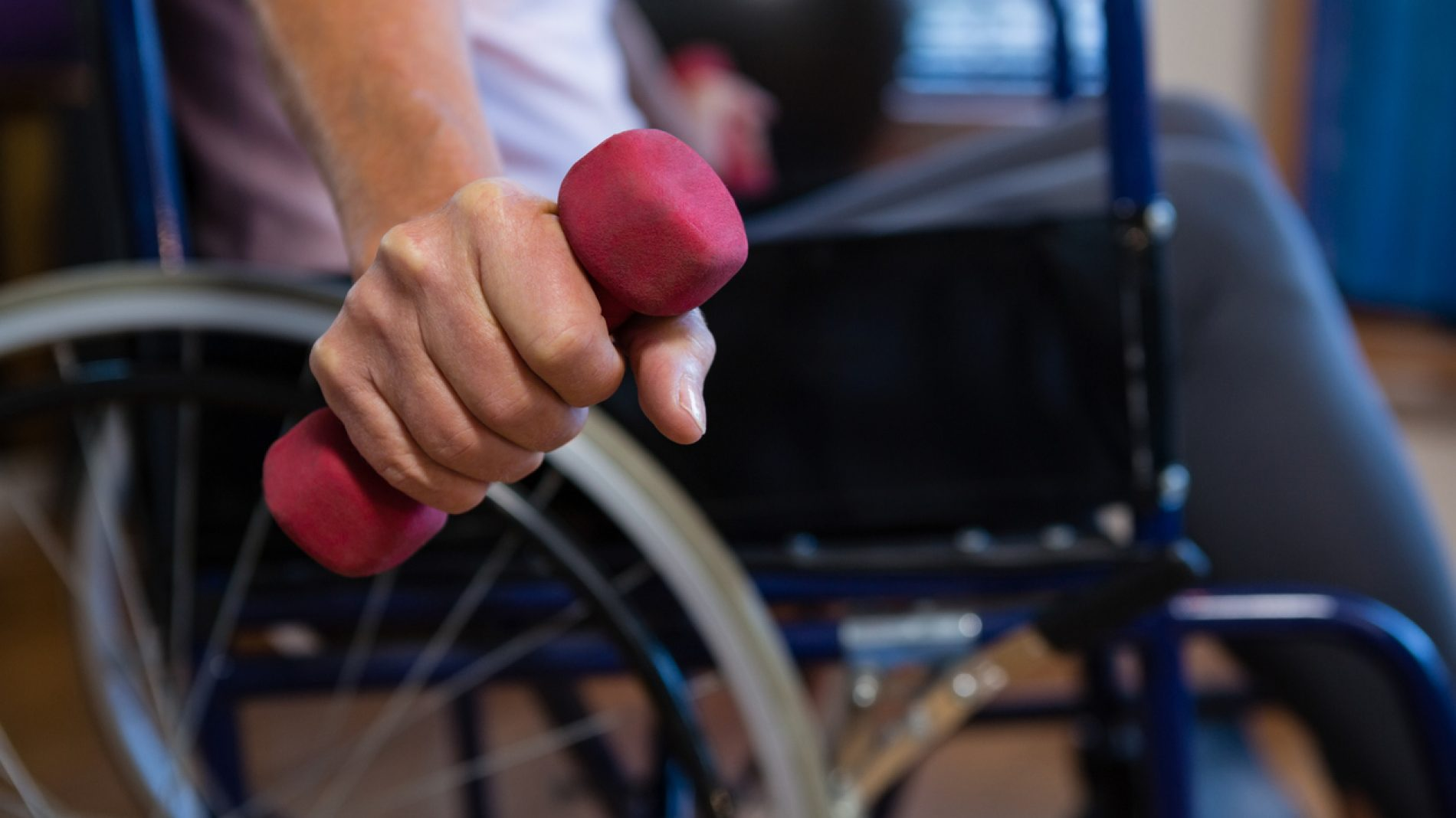 Senior woman in wheelchair performing exercise with dumbbell