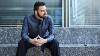 Young bearded Brazilian man leans forward confidently on a bench in the Financial District in New York City financial stress losing job