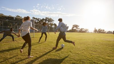 Friends playing football in the park