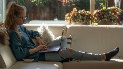 girl-sitting-on-the-white-couch-and-using-laptop_t20_koYlQP