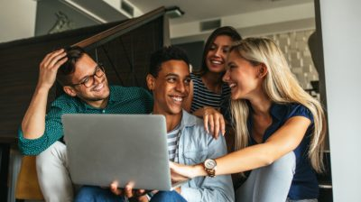 group-of-young-people-looking-at-laptop-edz8eC