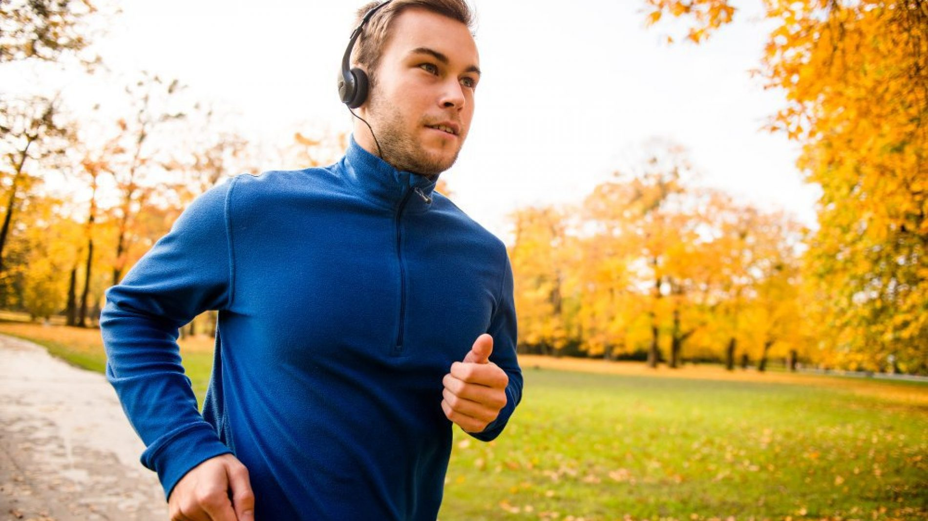 Young man with headphones running in autumn nature and listening music
