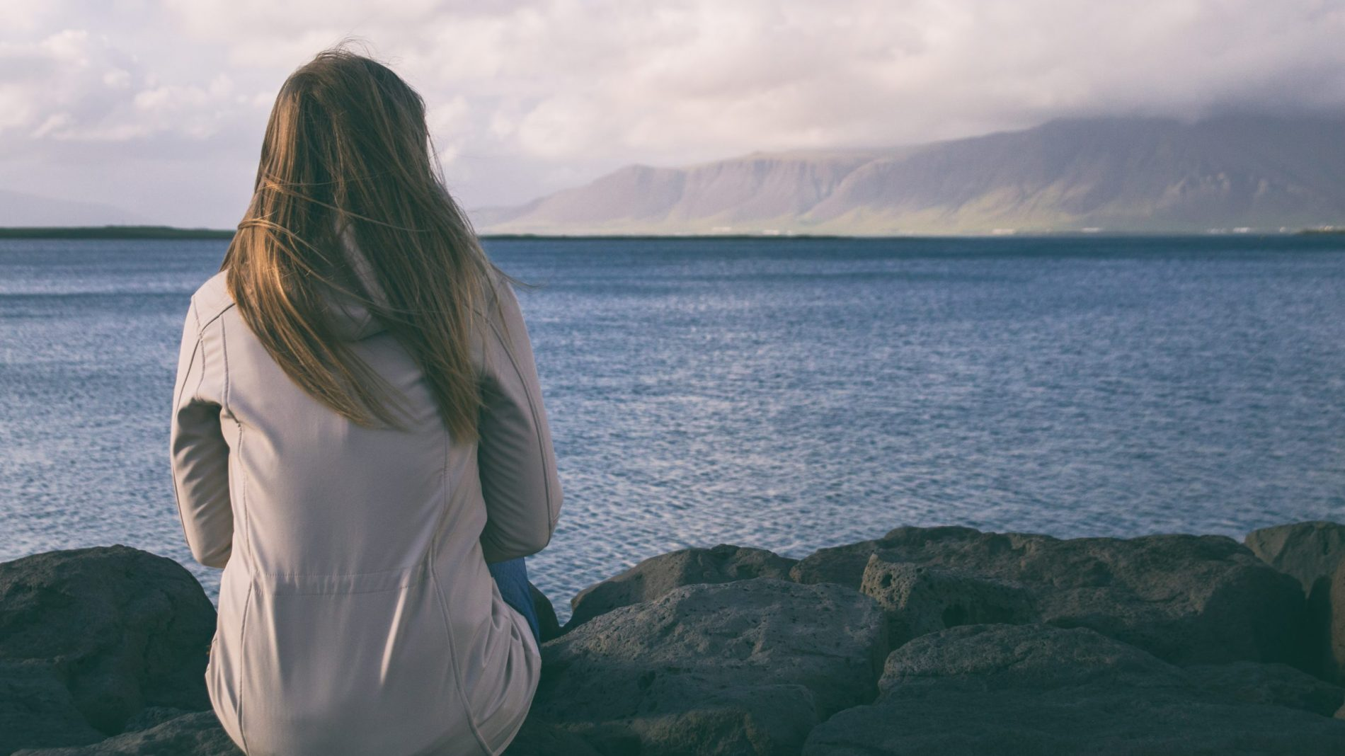 A woman sits looking out at the sea