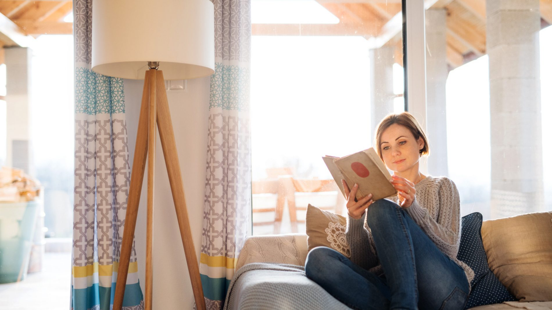 Woman reading on a couch at home