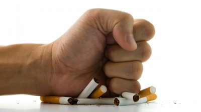 fist crushing a pile of cigarettes