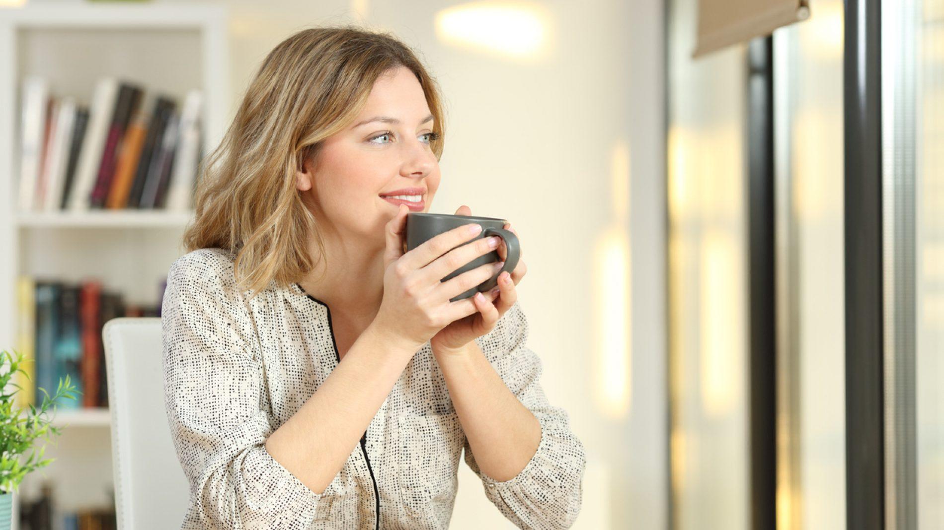 Woman looking through a window drinking coffee