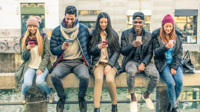 Group of people sitting looking at their smartphones
