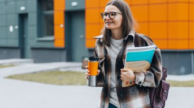 Student walking on a campus with coffee and books - going to college with an invisible disability